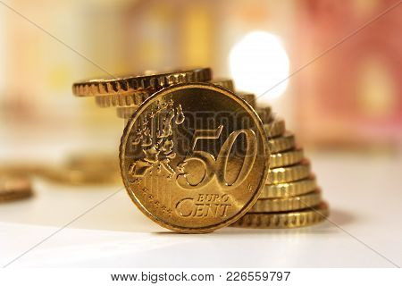 Euro Coin, Fifty Cents, Closeup, Stacked On White Desk With Euro Banknotes Behind