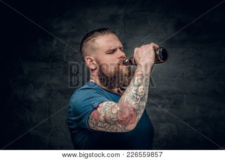 Fat Bearded Men With Tattoos On Arm Drinks Beer From A Bottle.