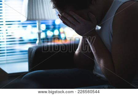 Sad And Unhappy Man Covering Face With Hands In Dark By Window. Burnout, Overwork Or Bankruptcy. Hea
