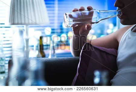 Alcoholic Sipping Bottle. Alcoholism And Alcohol Abuse Concept. Drunken Man Sitting Home On Couch. U