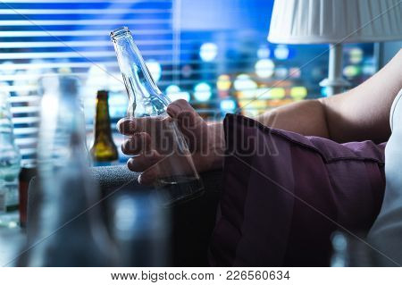Man With Drinking Problem Late At Night. Alcoholic Sitting On Sofa. Drunken Person Holding A Bottle.