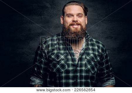 Smiling Bearded Male In A Green Plaid Shirt On Grey Background.