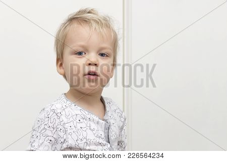 Playful Disheveled Cute Baby Looking At Camera Against White Background. Copy Space.