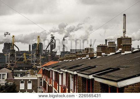 An Industrial Urban Scenery. There Are Houses' Roofs With Chimneys On The Foreground And A Metallurg