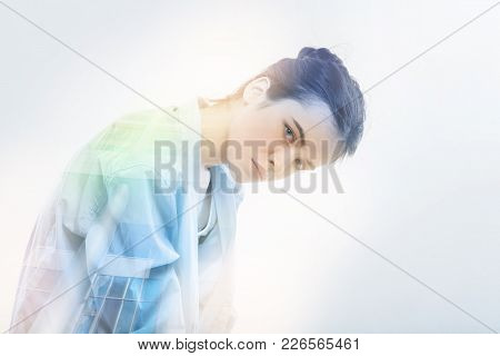 Leaning Down. Calm Young Tired Student Standing Round Shouldered And Looking Serious While Leaning H
