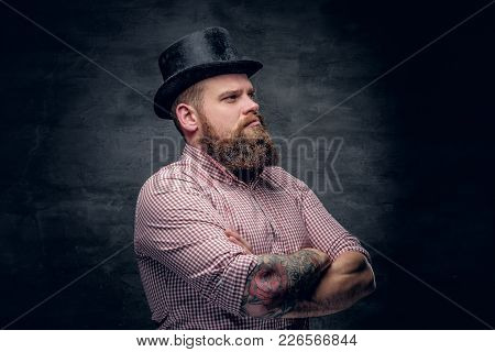 Bearded Male With Crossed Tattooed Arms Wearing Top Hat.
