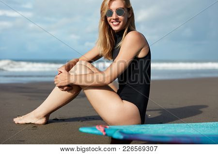 Blonde Girl In Swimsuit And Sunglasses, Sits Near Ocean, Ready For Surfing With Surfboard, Feels Rel