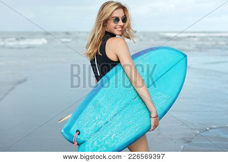 People, Hobby And Active Rest Concept. Glad Attractive Female Surfer Holds Big Blue Surfboard, Walks
