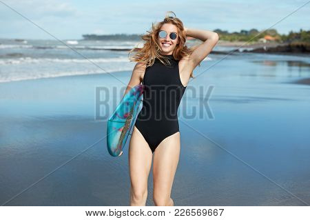 Happy Relaxed Female In Black Swimsuit And Sunglasses, Holds Surfboard Under Arm, Going To Have Surf