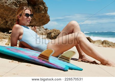 People And Good Vacation Concept. Relaxed Carefree Female In Swimsuit Lies On Sand Against Cliff And