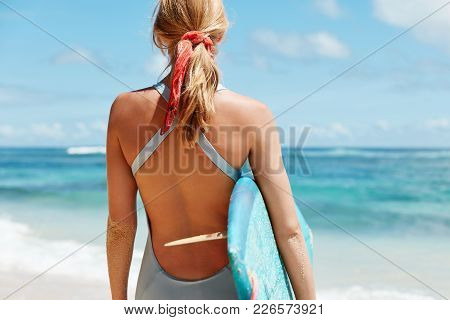 Cropped Back View Of Sporty Female Dressed In Swimwear, Has Light Hair Tied In Pony Tail Holds Surf