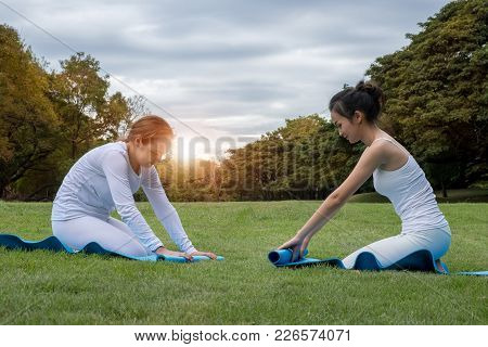 Two Attractive Young Women Folding Blue Yoga Or Fitness Mat After Working Out At The Garden. Healthy