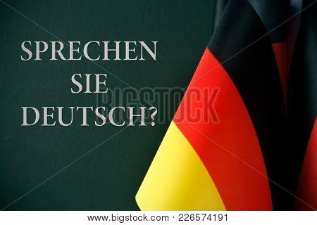 some flags of germany and the question sprechen sie deutsch?, do you speak german? written in german, against a dark green background