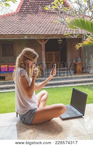 Girl Holding Cellphone, Coffe Mug With Laptop In The Garden Porch.