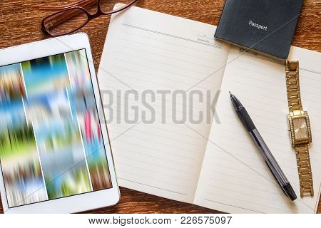 A Lay Flat Image With Tablet, Pen, Watch, Passport And Notepad. Travel Concept Image Showing Possibl
