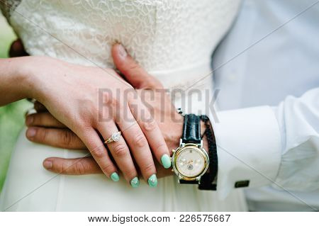 The Bride's Hand Lies On The Groom's Hand. Shows A Gold Engagement Ring. Wedding Ring. Stylish Manic