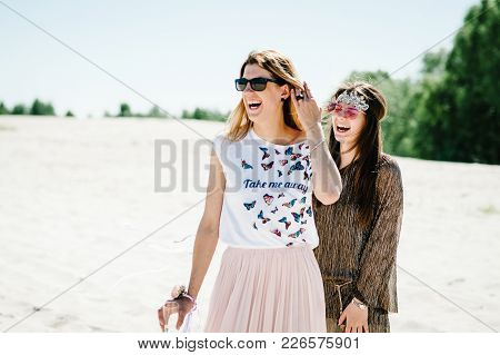 Beautiful Happy Stylish Sexy Young Two Girls With A Glass Of Wine, Champagne In Sand, Beach In Natur