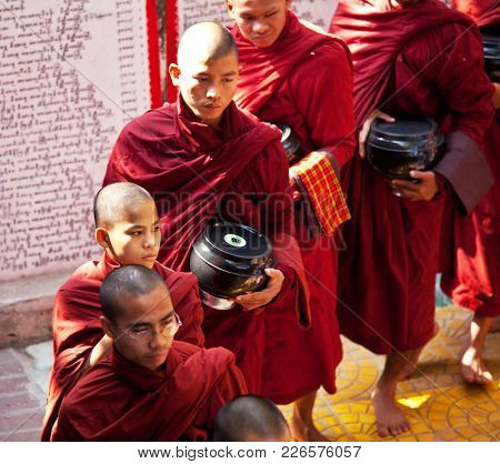 AMARAPURA, MYANMAR - FEBRUARY 09: Young monks are waiting in line for a lunch on February 9, 2011 in Maha Ganayon Kyaung monastery in Amarapura near Mandalay, Myanmar.