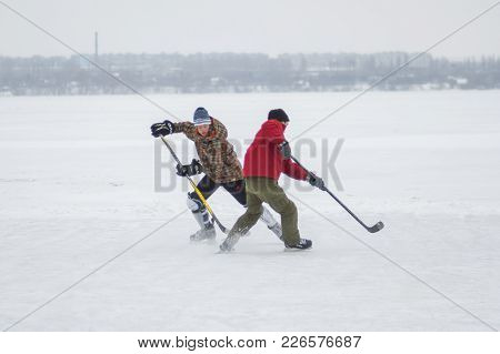 Dnipro, Ukraine - January 28, 2018: Teenager Boy Fight With Mature Man For The Puck While Playing Ho