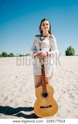 Portrait Beautiful Happy Slim Stylish Sexy Young Girl Standing On The Beach With A Guitar. Hand Deco