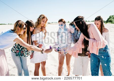 Beautiful Happy Stylish Sexy Young Girls Stand Beach And Light Up Colored Smoke Bombs. Show Sincere