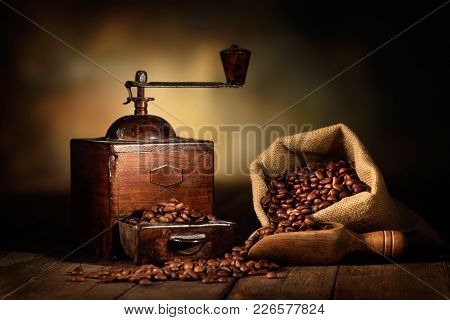 old grinder with coffee beans, jute bag and wooden scoop