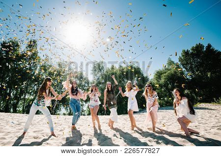 Beautiful Happy Stylish Sexy Young Girls Stand In Beach And Opens Colored Confetti On Background Nat