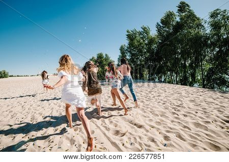 Beautiful Happy Stylish Sexy Young Girls Go Runs Back In Sand Beach Throwing Colored Confetti On Bac