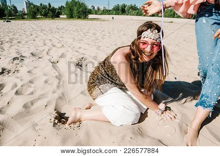 The Woman Is Sitting On The Sand. Beautiful Happy Stylish Sexy Young Girl Runs And Falls Down In San
