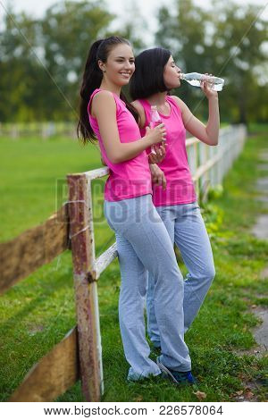 Beautiful Fitness Athlete Girls Resting Or Drinking Water Outdoor.
