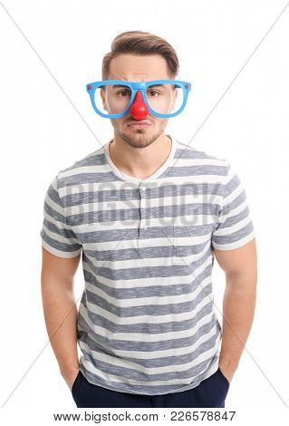 Young man in funny glasses on white background. April fool's day celebration
