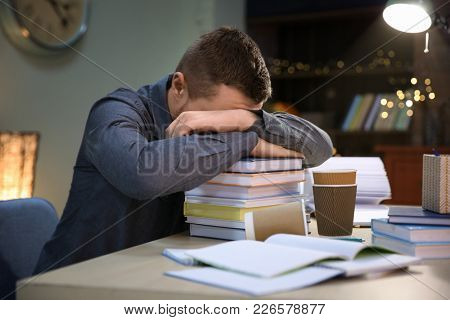 Tired student sleeping on stack of books at table indoors