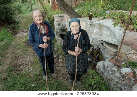 JERMA VALLEY, PIROT, SERBIA  - JULY 29, 2017: two unidentified old women with headscarf and walking stick posing for the camera in countryside near water spring