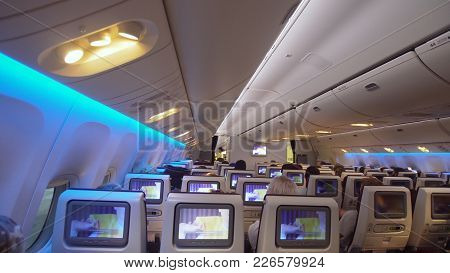 Interior Passengers Airplane With People On Seats. Aircraft Cabin With Rows Of Seats. Passengers Tra