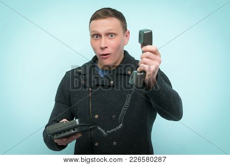 Surprised Hot Line Consultant Man Is Holding In Hands A Phone Handset Isolated On Blue Background. U