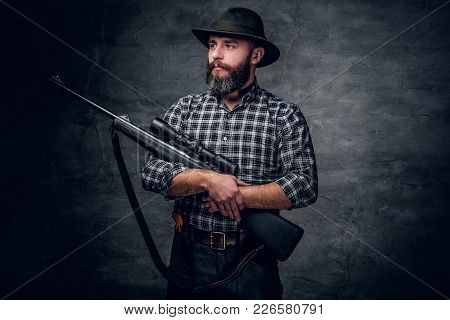 Studio Portrait Of Bearded Hunter Male Wearing A Plaid Fleece Shirt Holds A Rifle.
