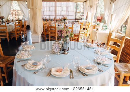 Decorated Tables In Sky-blue Color With Plates, Knives, Forks And Bouquet In Silver Vase On The Cent