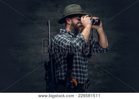 Studio Portrait Of Bearded Hunter Male Wearing A Plaid Fleece Shirt Looking Through Binoculars, Hold