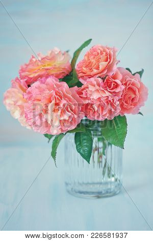 Delicate Beautiful Roses From A Garden In A Glass Vase On A Blue Background.