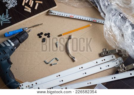 Tools, Furniture Parts, Wrapping Film, Screws On A Sheet Of Cardboard. Building Furniture Manually,