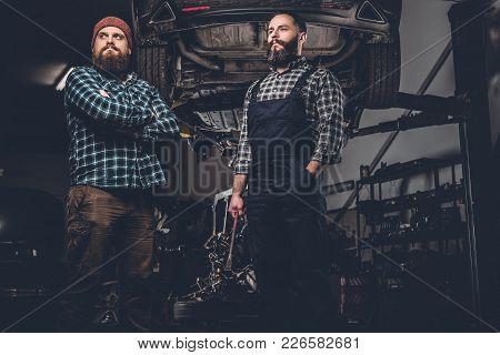 Portrait Of Two Bearded Mechanics In A Garage.