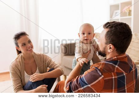 family, parenthood and people concept - happy mother, father and baby at home