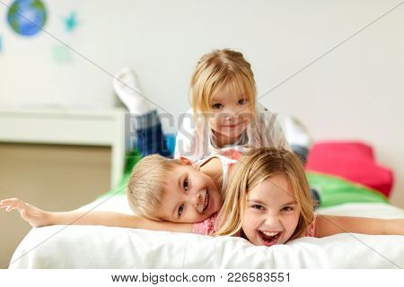 childhood, leisure and family concept - happy little kids having fun in bed at home