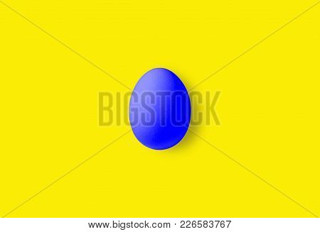One Blue Egg On A Yellow Background.  Minimalism Style