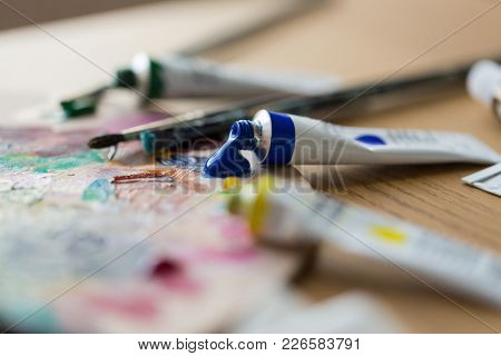 fine art, creativity, painting and artistic tools concept - acrylic color or paint tubes, palette and brushes