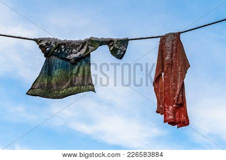 Two Pieces Of Washed Clothes With Some Snow On It, Drying On The Clothesline In The Winter. Blue Sky