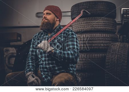 Portrait Of Bearded Mechanical Sits On An Old Tire In A Garage.