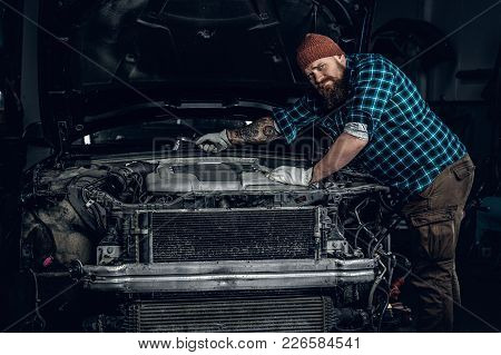 Bearded Mechanic With Tattoo On Arms Repairing A Car In A Garage.