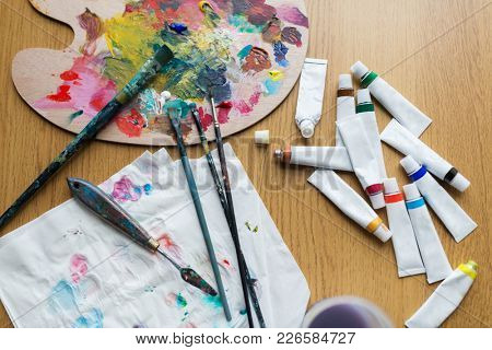 fine art, creativity and artistic tools concept - palette knife, brushes and paint tubes on table