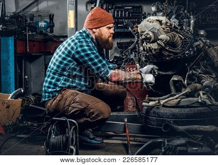 Bearded Fat Male Repairing Engine Of A Car In A Garage.